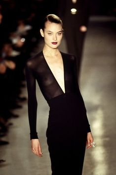 """The V-Front Jumpsuit - """"Bodysuit becomes jumpsuit, obviously,"""" riffs Karan. This deep-V style from Fall 1996 features a front zip, making it easy to put on and take off, and was sported on the runway by an angelic Shalom Harlow. """"The plunge neck is something that I always love because it elongates you,"""" Karan explains. The piece showed its full potential in that year's ad campaign, worn by Demi Moore, who leapt and crept through Peter Lindbergh's pictures like a glamorously clad acrobat. """"I…"""