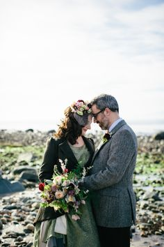 A bride with flowers in her hair stitched to a birdcage veil, bespoke green 1950s style wedding dress and tweed jacket.  From 'The Florist and The Fiddler ~ A Floral and Musical Inspired Wedding at Crear in Scotland'.  http://www.caroweiss.com/