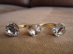 Anel em metal dourado com aplicação de três cristais swarovski brancos, sendo o do meio em formato de coração.  Aros 19 (diãmetro: 1,8cm) e 20 (diâmetro: 1,85cm) R$56,00