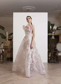 Strapless, light pink, see-through ball gown, with white and silver thread embroidery, a sculputral detail on the bust, and sparkling sequined stars, on tulle