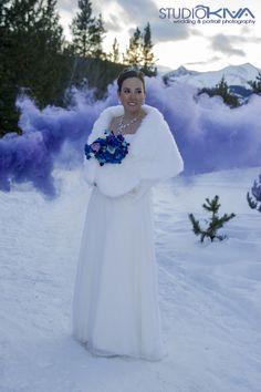 Winter bride with smoke bombs photo shoot. Long sleeveed wedding dress and bridal shawl. Blue and purple winter mountain wedding