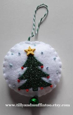 This listing is for ONE felt and glitter Christmas tree Christmas ornament/decoration Each ornament is made from white felt with a green glitter tree appliqued onto it. The tree is finished with a tiny red french knot baubles,a tiny yellow star button and french knots in pale blue