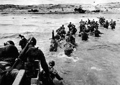 U.S. troops disembark from a landing vehicle on Utah Beach on the coast of Normandy, June 6th, 1944.