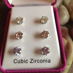 3  NWOT cubic zirconia earrings This is 3 pairs of cubic zirconia earrings. NWOT I purchased them in dress barn once with some clothing I never used them. They are clear pink and a light lavender. Equivalent to about a carat each stone so they are not small. Comes in original box. Silver plated posts and backs. This is a great gift for a co worker or a young lady or if you have multiple holes. Independent design  Jewelry Earrings