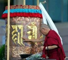 The Dalai Lama prays by Tibetan Prayer Wheel