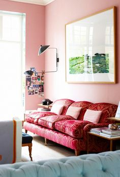 Living space with pink walls, a pink sofa, and a black wall sconce