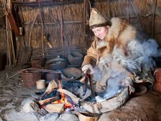 Mesolithic girl at a fire, making a new wooden bowl - Archeon, Archaeological Open Air Museum in the Netherlands