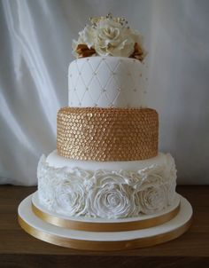 Cream and gold wedding cake with rose ruffles, edible gold sequins and quit pattern. Topped with cream sugar roses, gold mini flowers and gold diamonte