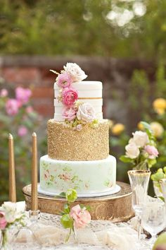 3-tiered gold wedding cake with flower details for an outdoor shabby chic wedding.