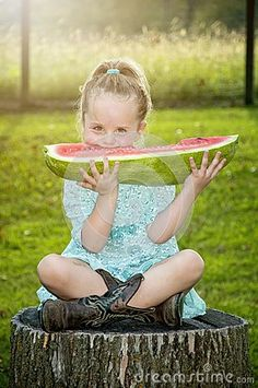 Little girl holding and eating huge slice of watermelon