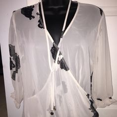 New York & Company Blouse Sheer cream and black print blouse with necklace attached made of same material. Both the cuffs and bottom of blouse have elastic to creat a ruffled look. The sleeves are 3/4 length. New York & Company Tops Blouses