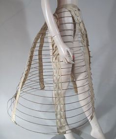 1860's steel-wire hoop-cage/crinoline with 20 fabric-covered hoops, seven riveted linen tapes, a linen waistband and a patent-dated 1866 buckle, measures 27-inches at the waist, 34-inches long and 88-inches in circumference at the bottom hoop.