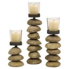 """Three iron and glass candleholders with stacked stone bases.    Product: Small, medium, and large candleholderConstruction Material: Stone, glass, and ironColor: NaturalAccommodates: (1) Candle each - not includedDimensions:  Small: 6.5"""" H x 2.75"""" Diameter Medium: 9"""" H x 2.75"""" DiameterLarge: 11.25"""" H x 2.75"""" Diameter"""