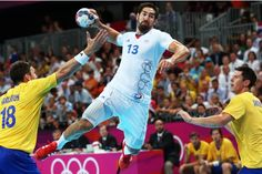 France's Nikola Karabatic, center, leaps in the air to score past Sweden's Tobias Karlsson, left, and Sweden's Kim Andersson, right, during the men's handball gold medal match at the 2012 Summer Olympics, Sunday, Aug. 12, 2012, in London.