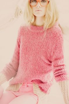 pink sweater; glasses.