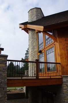 This is a picture of a beautiful stone chimney that towers above the open deck. The chimney shown services an interior and exterior fireplace. So the homeowner can enjoy a fire in either location. For more on custom design please follow the link below. - John  http://www.northtwinbuilders.com/new-home-construction-design-layout