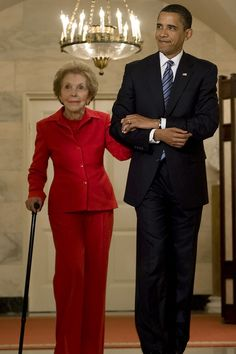 President Barack Obama walks with Nancy Reagan in the Diplomatic Room of the White House in 2009.