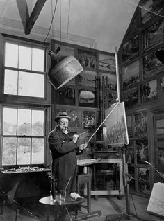 """Caption from the January 7, 1946, issue of LIFE. """"Churchill stands in his studio at [his home] Chartwell, Kent, dressed in his RAF-blue siren suit, and peers over his spectacles at the camera while retouching one of his old landscapes."""""""