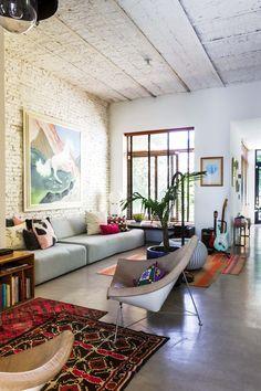 En esta casa moderna en La Lucila, un sillón de tres cuerpos en el que se agrupan varios almohadones juega en sintonía con el cuadro del unicornio firmado por Hernán Salamanco.
