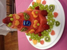 """My best friends daughter wanted a """"fruit cake"""" for her 5th birthday. This turned out super cute, and was very easy! First I sliced the watermelon, then placed octagons (printed off the computer and cut out) onto the slices so I knew where to cut. Using cookie cutters we made the hearts from cantaloupe and kiwi (the grapes are held on with tooth picks). We used chopsticks to hold all 4 tiers together. The thinner your hearts are, the better they stick to the watermelon. Good luck!"""