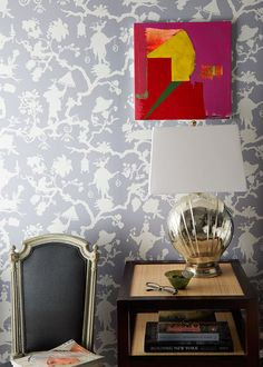 A chrome lamp sits on a raffia-topped bedside table, backed by a modern Chinoiserie-style wallpaper. | Lonny.com