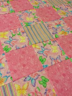 The front of this adorable quilt is made with multi-colored stripes, pink with butterflies, and pink with swirls fabric squares. The back is a solid pink Minky Cuddle Dimple Dot fabric.  The fabric on the front of this quilt is 100% cotton. The Minky on the back is 100% polyester. Inside is Warm and Natural batting. The approximate measurements are as follows:  Baby - 27 x 39 inches Toddler - 39 x 51 inches  This quilt will not be washed. It may be washed in cold water on the delicate cycle…