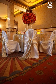 Ivory chair covers, gold sequin chair sash.  Soft gold sequin tablecloth. Tall hot pink, coral and red rose centerpieces. http://www.partyplannerdenver.com
