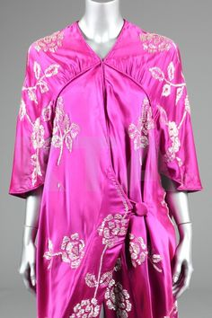 Reville & Rossiter deep magenta-pink satin opera coat, 1912, with dated embroidered satin label, the draped wrap-over front panels with piped seams, button to one hip, embroidered overall with large pearlised roses and foliage