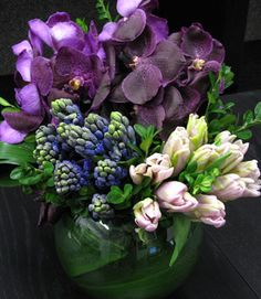 Lovely Vanda Orchids from Thailand accent the arrangement with clusters of Parrot Tulips and Hyacinths from The Netherlands creating an impressive piece.