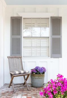 Beautiful white home exterior walls frame a window finished with gray shutters positioned above a rustic slated back outdoor chair topped with a gray and white striped cushion and sat on red brick floors beside a gray pot filled with purple hydrangeas.