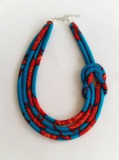 Blue African wax print necklace knotted at the side to create a trendy and fun statement piece which can be dressed up or down. - The necklace measures approximately 20 inches has a 2 inch extender chain for length adjustment. Please choose your preferred length before you checkout. - It is made of African wax print and cotton stuffing. The fabric colour is blue with wine colour patterns. - It has a matching beaded earrings. - Do not sleep, bath or exercise while wearing this necklace. Do…