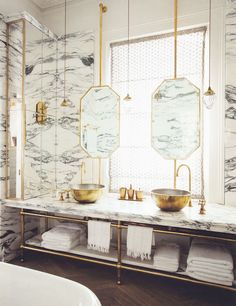 Gold accents are one of many concepts to love about this bathroom. Another is the open towel storage beneath the sinks. Let's call this minimalistic-chic!