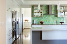 Kitchen featuring glass mosaic splash-back by John Croft Design.