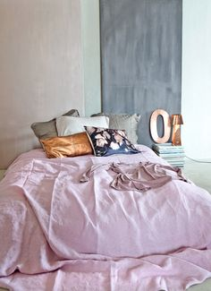 Pink bed full of pillows - sexy material, soft, floral, satin, rich feeling. 'Let the mat materials in the base predominate, so that the luster of copper additional strikes.' - Styling Marianne Luning - Photography Anne de Leeuw