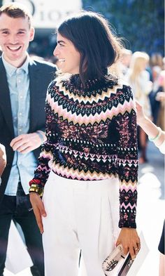 Leandra Medine wears a graphic sweater, stacked bracelets, and white trousers | Image via whowhatwear.com