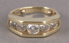 A gold and diamond band ring.  14KT yellow gold band. with five graduated channel set ring. Size 2 0.17 t oz.