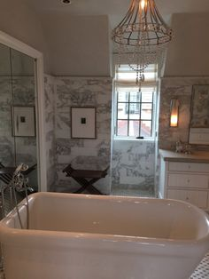 Timeless bathroom design. Doors to closet and shower are disguised behind the panels of mirror. Brilliant!