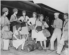 """War correspondents leaving from the Camp Patrick Henry, Virginia, enroute overseas. L to R: John Chabat Smith; 1st Lieutenant Donald E. Higgens; Marcella Bailey; Virginia Rathbun; Barbara V. Laird; Helen Angell; Cecilia (Jackie) B. Martin, correspondent and photographer for the Ladies"""" Home Journal; R. Annuniata Axlund, (seated) Casper, Wyoming. Official Photograph, US Army Signal Corps, Hampton Roads Por of Embarkation, Newport News, Virginia ~"""
