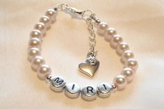 Pearl bead bracelet with silver coloured alphabet beads. Bracelet is child's size but comes with an extension chain so will fit the recipiant as they grow up!   Silver plated clasp, extension chain and heart charm.     From £5