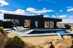 The pool is framed by angular concrete paths reflecting the natural geometry of the site.