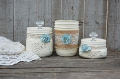 Shabby chic mason jar dresser or bathroom set. Hand painted in soft ivory, lightly distressed, wrapped with burlap, lace and seed pearl trim, with dusty blue roses, finished with a protective coating.