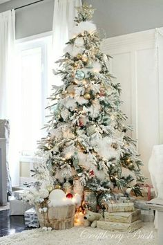 Beautiful Christmas tree with snowy branches and lots of white decor. Christmas tree. Home decor