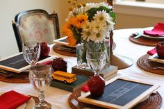 """first day of school dinner decor: """"I made chalkboard place cards for the table and then perched an apple on each of the chalkboards. In the center of the table there was a vintage globe, a school bus and a bouquet of flowers on top of a pile of vintage books."""""""