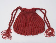 Beaded knit flapper evening bag,1925    Bead knitting incorporates beads into the design by stringing the beads on the knitting yarn. This technique began in the early 19th century. It remained popular as late as the early 20th century. The bead knitted item rarely has the bead loss seen when beads are stitched onto a cloth surface.  The bag is knitted with cranberry red cotton yarn and decorated with red glass beads. It is lined with matching silk. It has a drawstring top w/tassels at the…