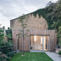 Slender batons of untreated larch cover two extensions erected in the garden of this semi-detached home in London by Haptic