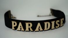 Finish off your look with this PARADISE super cute Letter Choker necklace.Take your outfit to the next level with this black wooden choker. * Length: 30 cm * Width: 2 cm * Chain link whit lobster clasp * Letters material: wood * Band material: elastic Available in black,red and white color