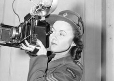 Sergeant Karen M. Hermiston of the Canadian WomenÕs Army Corps (C.W.A.C.), who is holding an Anniversary Speed Graphic camera, London, England, 15 November 1945.