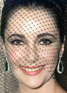 Elizabeth at the London Palladium 1965 wearing Dior, with her famous emerald earrings by Bulgari