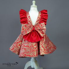 The Cindy Lou Dress is a fashionable take on traditional girls' holiday dresses. It is made from a rich, heavy red jacquard fabric with metallic gold threads. I