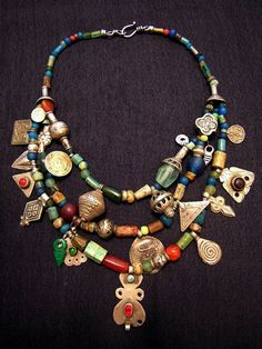 by Anna Holland | Necklace; Ancient Roman glass beads, 1800BC-350BC, made from pottery found by farmers in Balkh, also known as Bactria, one of the world's oldest cities, in present-day northern Afghanistan. Small glass beads and silver Berber pendants from Morocco. Carnelian, silver, and glass beads, pendants, and dangles from the Turkoman, Sindhi, and Uzbek peoples. Chinese green glass beads. Indonesian Java beads. And other beads from around the world. | Sold